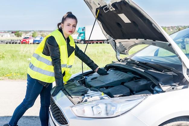 Belle femme vérifiant le moteur de la voiture sur le bord de la route