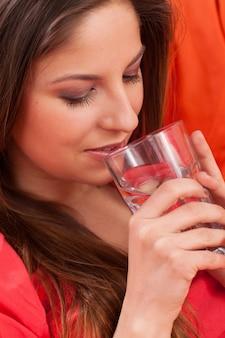 Belle femme avec un verre à la maison