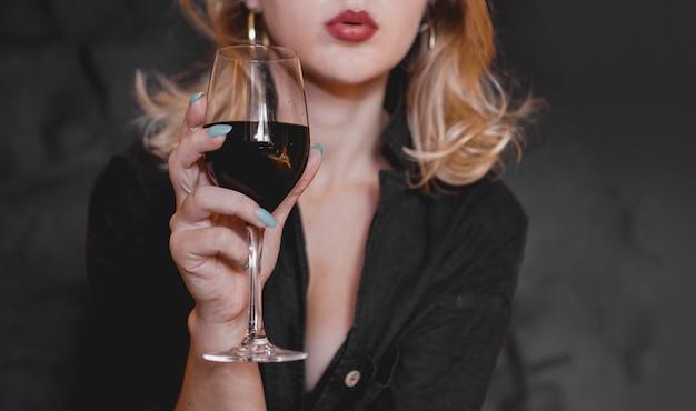 Belle femme avec verre de vin rouge - mise au point sélective.