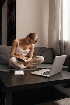 Belle femme en vêtements décontractés est assise sur un canapé dans un appartement et est engagée dans l'auto-apprentissage, prend des notes dans un ordinateur portable à côté d'un ordinateur