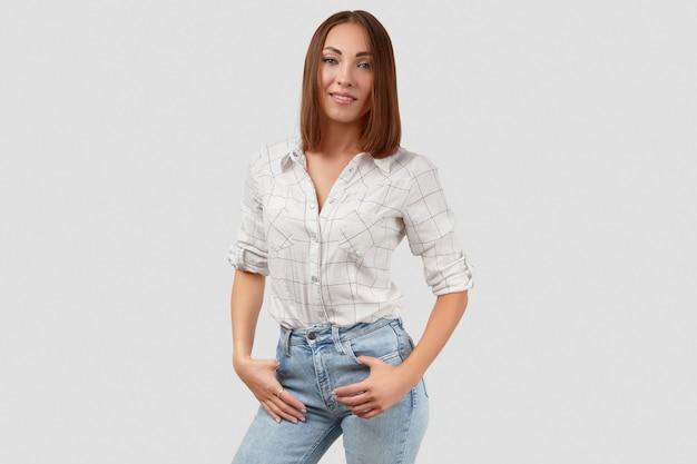 Belle femme en vêtements décontractés posant sur fond blanc