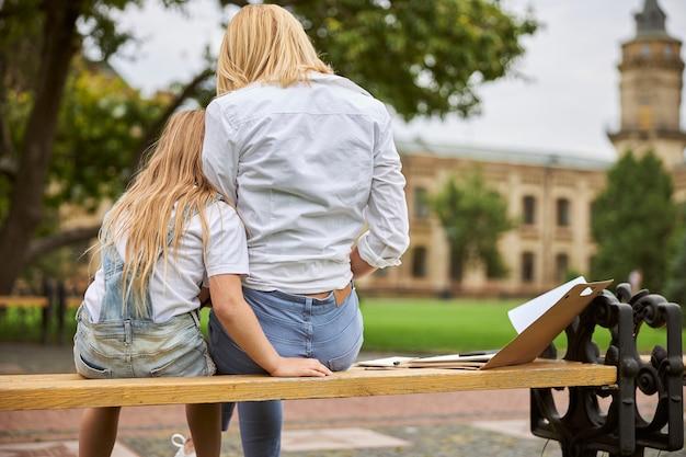 Belle femme en vêtements décontractés avec sa fille en barboteuse en jean passer du temps ensemble dans le parc