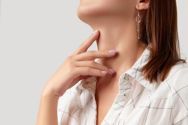 Belle femme en vêtements décontractés touche son cou sur fond blanc avec espace de copie