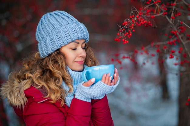Belle femme en vêtements d'hiver, boire du thé