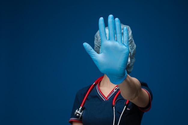 Belle femme en vêtements médicaux blancs, masque, gants bleus et phonendoscope sur ses épaules, photo isolée sur un espace bleu