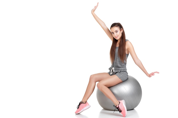 Belle femme en vêtements de sport assis sur un ballon de fitness isolé sur fond blanc