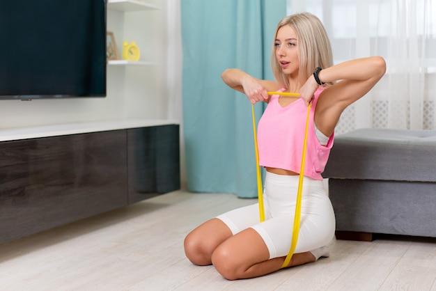 Belle femme en vêtements sportifs de mode faisant exercer avec une bande jaune à la maison. séances d'entraînement à domicile