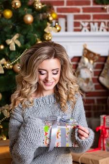 Belle femme en vêtements tricotés regarde sur le cadeau dans ses mains à l'arrière-plan du nouvel an intérieur avec arbre de noël