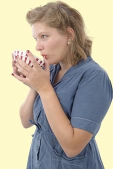 Belle femme avec des vêtements vintage boire un café