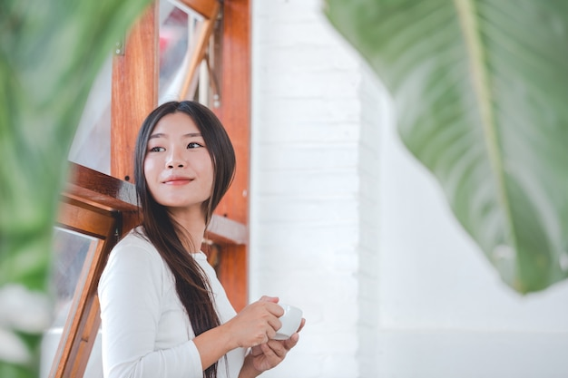 Une belle femme vêtue d'une chemise blanche à manches longues assis dans un café