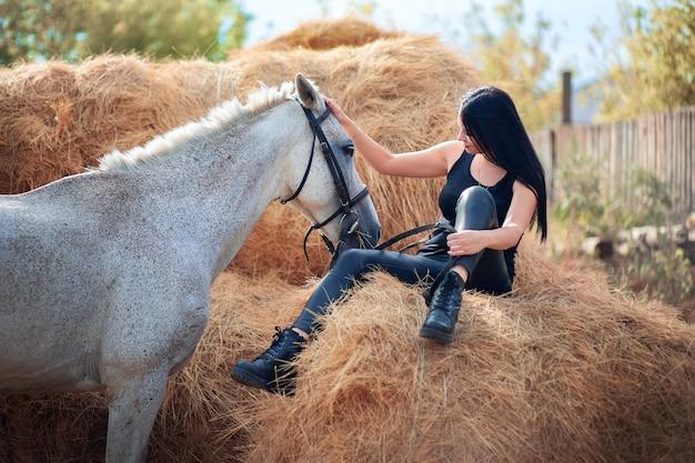 Une belle femme vêtue de cuir noir est assise dans le grenier à foin et caresse un cheval gris. thème de la ferme et des animaux de compagnie