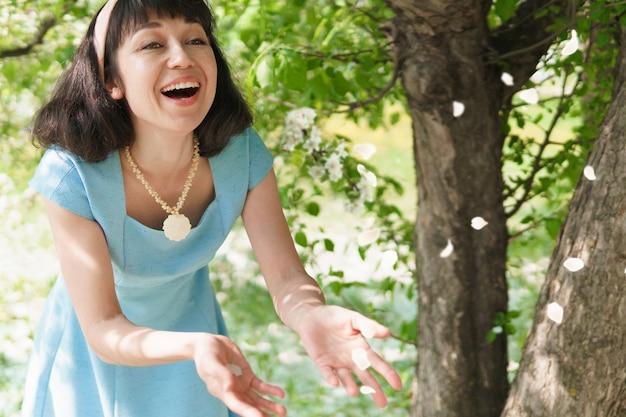 Belle femme vêtue d'une longue robe bleue avec des pommiers en fleurs dans le jardin de printemps, elle jette des pétales de fleurs