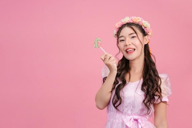 Une belle femme vêtue d'une princesse rose joue avec son bonbon sucré sur un rose.