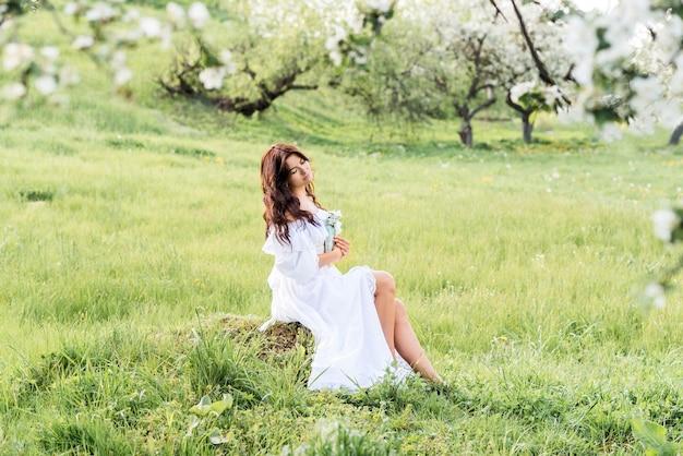 Belle femme vêtue d'une robe blanche lit un livre dans le jardin de printemps. une fille sur le fond des arbres en fleurs.