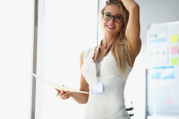 Une belle femme vêtue d'une robe blanche se tient dans le bureau et tient des documents féminins élégants