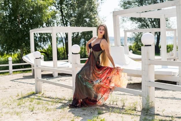 Belle femme vêtue d'une robe élégante posant sur la plage