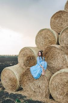 Belle femme vêtue d'une robe sur des meules de foin.