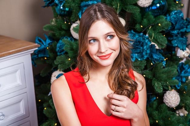 Belle femme vêtue d'une robe rouge, levant les yeux et rêvant. prise de vue en intérieur