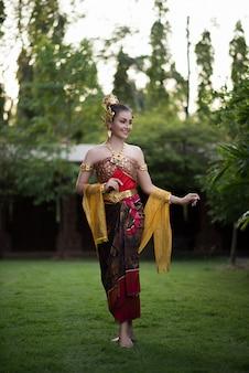 Belle femme vêtue d'une robe thaïlandaise typique