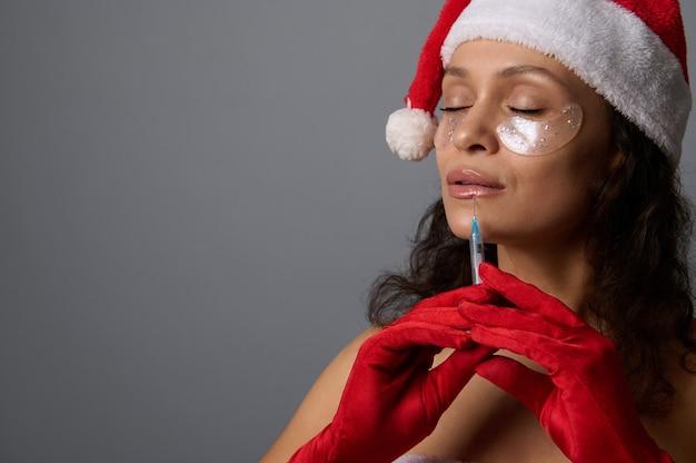 Belle femme vêtue d'une tenue de carnaval de santa, avec des taches sous les yeux recevant une injection de beauté sur ses lèvres. concept d'augmentation des lèvres pour la publicité de noël pour les salons de beauté esthétiques.