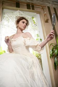 Belle femme victorienne, robe blanche à la maison