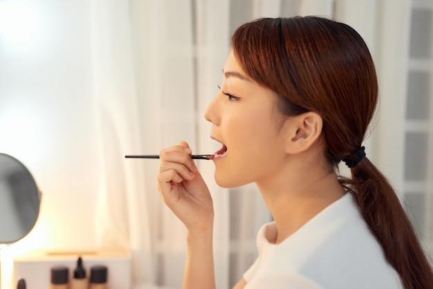 Belle femme avec un visage de beauté appliquant un baume à lèvres, un bâton de soin des lèvres. concept de cosmétiques de soins de la peau des lèvres.
