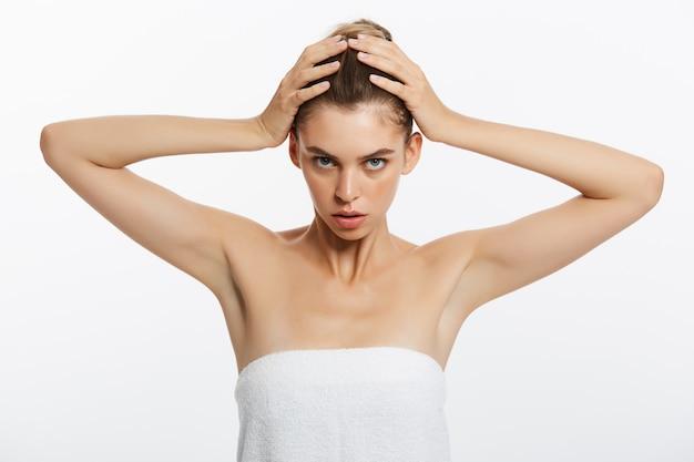 Belle femme visage bouchent studio blanc