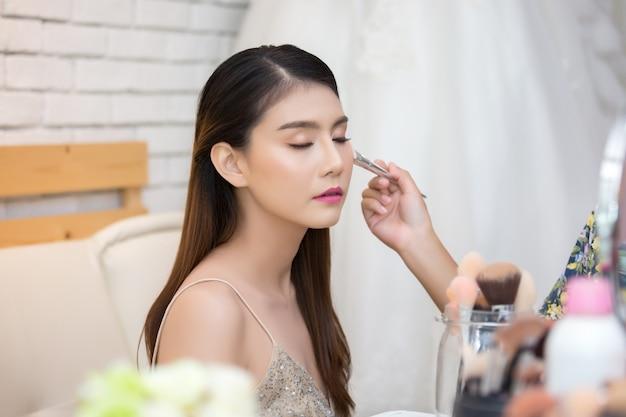 Belle femme visage et main de maquillage