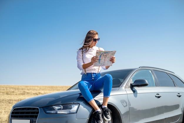 Belle femme voir la carte pour les voyages. jolie fille debout à côté de la voiture. le plaisir de voyager