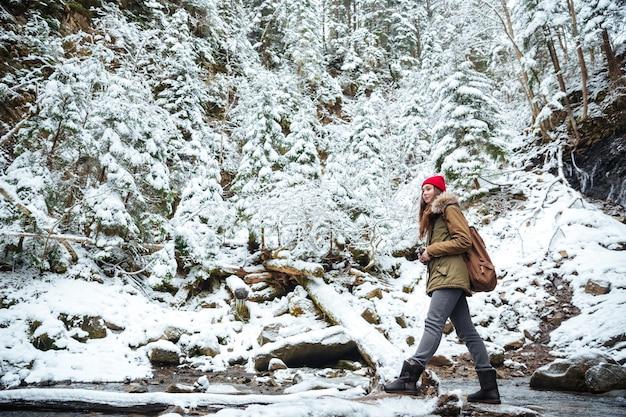 Belle femme voyageant dans la forêt d'hiver