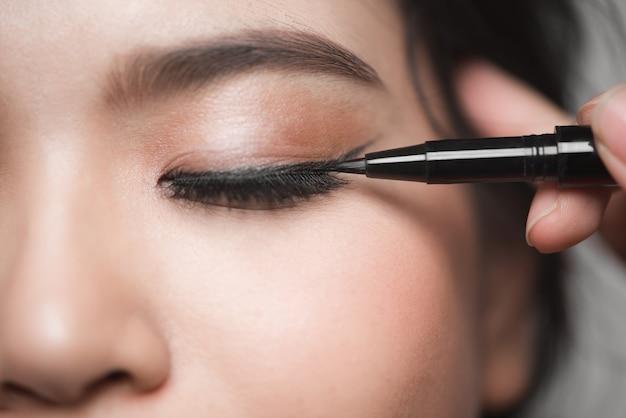 Belle femme avec des yeux de maquillage lumineux avec du maquillage noir