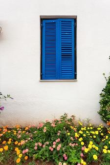 Belle fenêtre bleue dans le style grec à la vieille maison