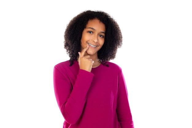 Belle fille adolescente avec appareil dentaire isolé sur un mur blanc