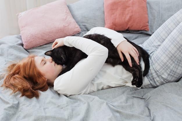 Belle fille adolescente avec chat noir sur le lit à la maison