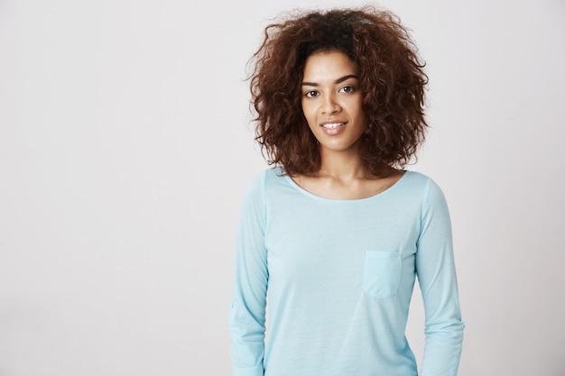 Belle fille africaine en chemise bleue souriante.