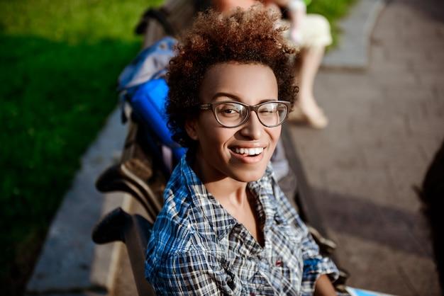 Belle fille africaine souriante, un clin de œil, assis sur un banc dans le parc.