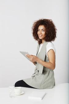 Belle fille africaine souriante tenant la tablette assis sur le lieu de travail. copiez l'espace.