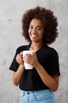 Belle fille africaine tenant la tasse sur le mur lumineux.