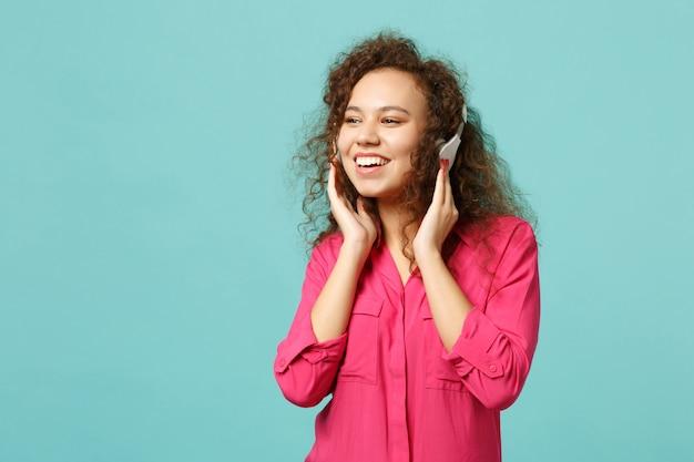 Belle fille africaine en vêtements décontractés regardant de côté, écoutant de la musique avec des écouteurs isolés sur fond bleu turquoise en studio. les gens émotions sincères, concept de style de vie. maquette de l'espace de copie.