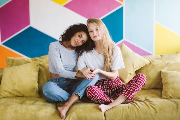 Belle fille afro-américaine aux cheveux bouclés foncés, penchant la tête sur jolie fille aux cheveux blonds rêveusement tout en se tenant la main avec un mur coloré