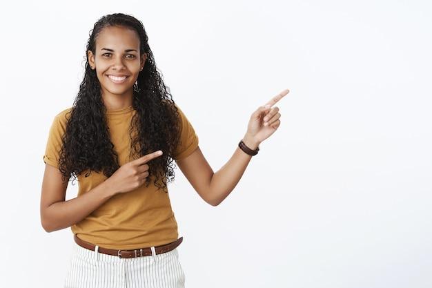 Belle fille afro-américaine aux cheveux bouclés pointant du doigt le coin supérieur droit à la publicité