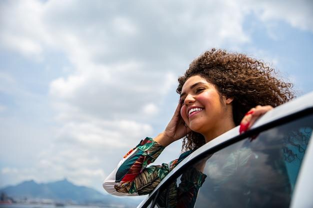 Belle fille afro-américaine avec une coiffure afro souriant côté une voiture