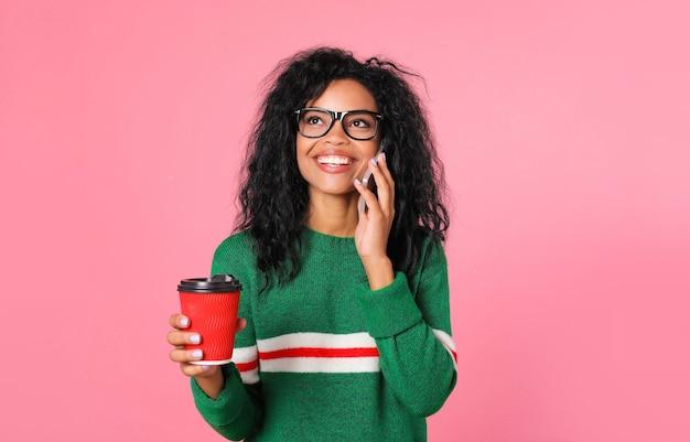 Belle fille afro-américaine dans un sweat-shirt vert et des lunettes noires pose avec une tasse de café rouge dans sa main droite et un smartphone près de son oreille gauche