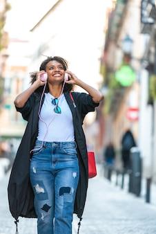 Belle fille afro-américaine, écouter de la musique sur un casque à l'extérieur.