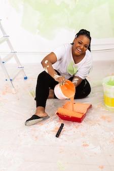 Belle fille afro-américaine peignant le mur avec un rouleau à peinture. portrait d'une jeune belle