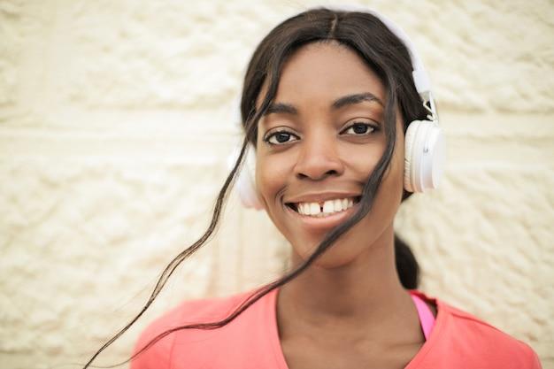 Belle fille afro écoutant de la musique