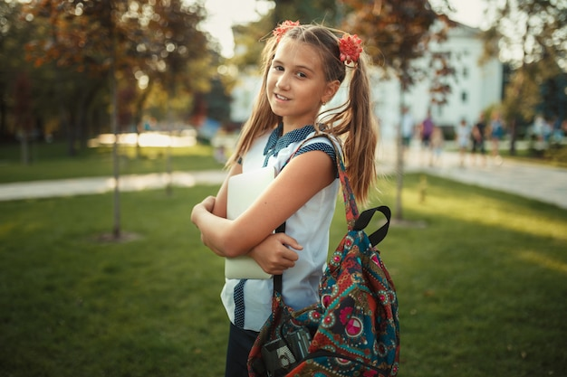 Une belle fille d'âge scolaire est debout près d'un arbre et tient une tablette. écolière portant une jupe et une chemise avec des chaussures