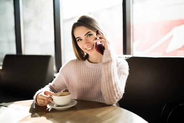Belle fille à l'aide de son téléphone portable au café pendant le frein à café après l'étude de travail