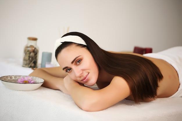 Belle fille allongée sur la table enveloppée dans une serviette dans le spa