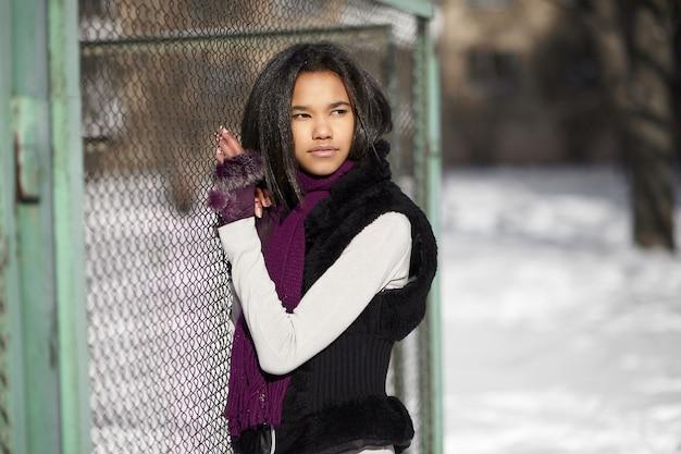 Belle fille américaine souriante assise dans la neige à l'extérieur jouant avec de la neige